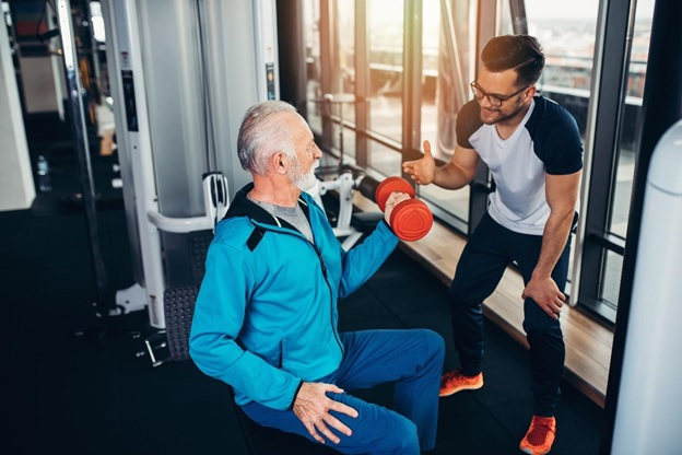 physical therapist helping a patient strengthen his arm muscles