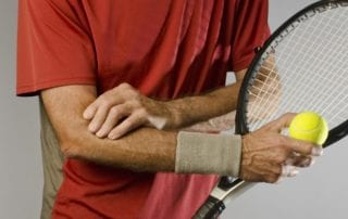 Tennis player holding his painful elbow