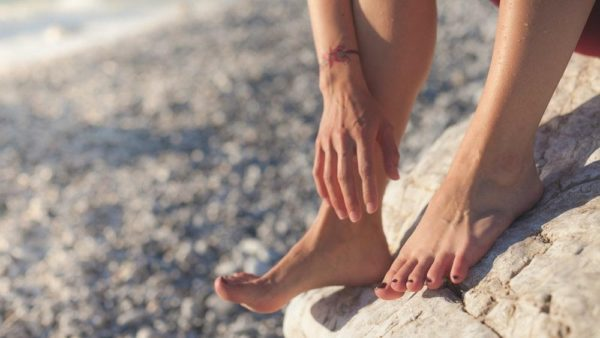 person resting their bare feet on a rock