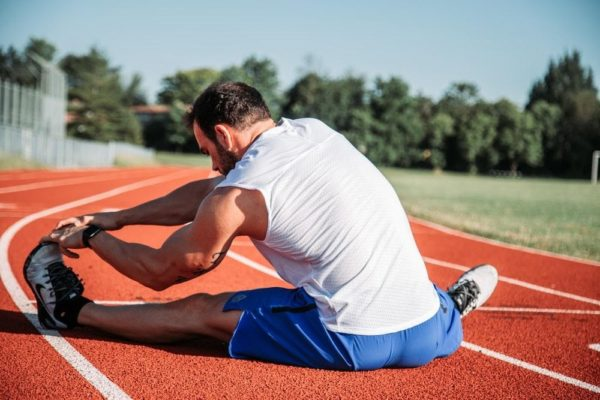 runner stretching his foot on a track