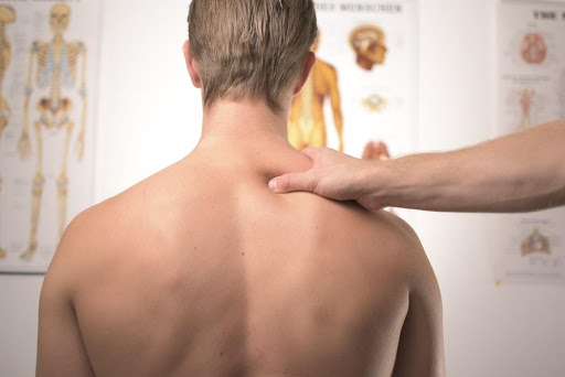 physical therapist diagnosing a patient's back pain